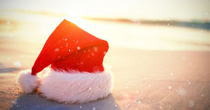 Composite image of snow falling. Snow falling against santa hat on the beach Royalty Free Stock Images