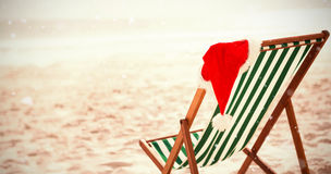 Composite image of snow falling. Snow falling against santa hat kept on empty beach chair Royalty Free Stock Photo