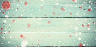 Composite image of snowflakes. Snowflakes against painted blue wooden planks stock images