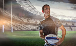 Composite image of sober rugby player holding ball Royalty Free Stock Photography