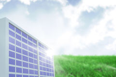 Composite image of solar panel against green landscape. Solar panel against white screen against sky over green field Stock Images