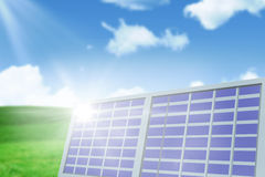 Composite image of solar panel against landscape. Solar panel against white screen against blue sky over green field Stock Image