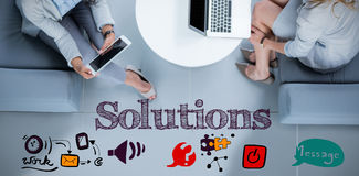 Composite image of solutions text message. Solutions text message against businesswomen using laptop and digital tablet Stock Photo