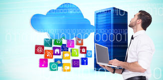 Composite image of sophisticated businessman standing using a laptop. Sophisticated businessman standing using a laptop  against composite image of cloud with Royalty Free Stock Photos