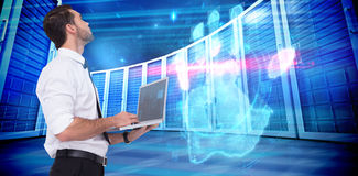 Composite image of sophisticated businessman standing using a laptop Royalty Free Stock Images