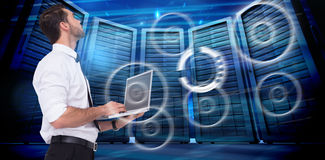 Composite image of sophisticated businessman standing using a laptop. Sophisticated businessman standing using a laptop  against composite image of server room Stock Photography