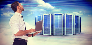 Composite image of sophisticated businessman standing using a laptop. Sophisticated businessman standing using a laptop  against composite image of server towers Stock Photo