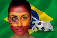 Composite image of spanish football fan in face paint Stock Photo