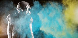 Composite image of splashing of blue color powder. Splashing of blue color powder against american football player standing with rugby helmet royalty free stock images