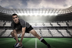 Composite image of sports player in black jersey stretching with ball Stock Photos