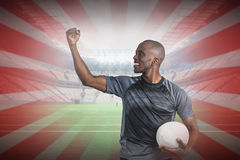 Composite image of sportsman with clenched fist holding rugby ball after victory Royalty Free Stock Image