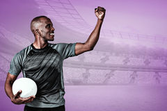Composite image of sportsman with clenched fist holding rugby ball after victory Royalty Free Stock Images