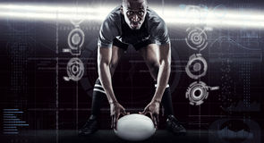 Composite image of sportsman holding ball while playing rugby. Sportsman holding ball while playing rugby against spotlights stock photos