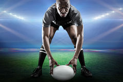 Composite image of sportsman holding ball while playing rugby Royalty Free Stock Photo