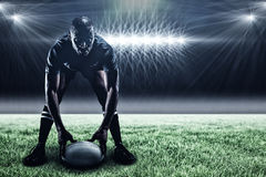 Composite image of sportsman holding ball while playing rugby and 3d. Sportsman holding ball while playing rugby against spotlight and copy space 3d stock image