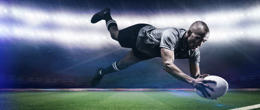 Composite image of sportsman jumping for catching rugby ball Stock Image