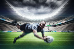Composite image of sportsman jumping for catching rugby ball Royalty Free Stock Photo