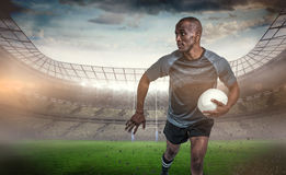 Composite image of sportsman running while holding rugby ball Stock Photos