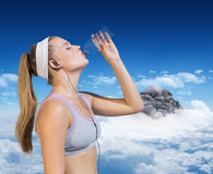 Composite image of sporty blonde drinking water Royalty Free Stock Photography