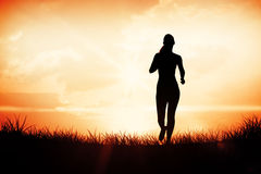 Composite image of sporty blonde jogging towards camera Royalty Free Stock Photography