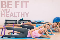 A Composite image of sporty people with exercising rings in fitness studio Stock Photography