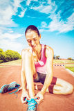 Composite image of a sporty woman doing her shoelace royalty free stock photography