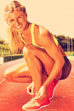 Composite image of sporty woman doing her shoelace royalty free stock image