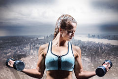 Composite image of sporty woman lifting dumbbells Stock Image