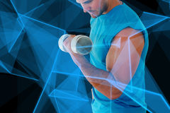 Composite image of sporty young man with dumbbell in gym Royalty Free Stock Image