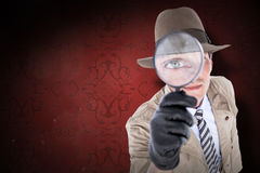 Composite image of spy looking through magnifier Stock Photo