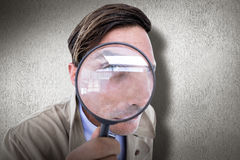 Composite image of spy looking through magnifier Royalty Free Stock Photography