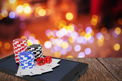 Composite image of stack of casino tokens with playing cards and dice on smartphone Royalty Free Stock Images