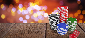 Composite image of stack of colorful casino tokens by red dice Royalty Free Stock Image