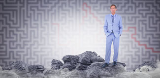 Composite image of standing businessman. Standing businessman against grey maze Standing businessman on white background Stock Photo