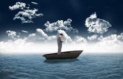 Composite image of standing businessman typing on his laptop in a sailboat Royalty Free Stock Image