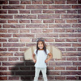 Composite image of standing girl with fake wings pretending to be pilot. Standing girl with fake wings pretending to be pilot against red brick wall Royalty Free Stock Photos