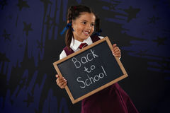 Composite image of star shapes on black scribbling. Star shapes on black scribbling against smiling schoolgirl holding slate with text against blackboard Royalty Free Stock Photography