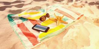 Composite image of starfish with sunglasses and mobile phone kept on beach blanket Stock Images