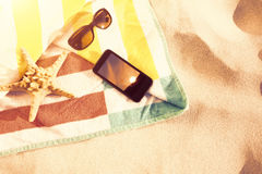 Composite image of starfish with sunglasses and mobile phone kept on blanket Stock Image