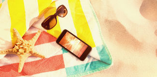 Composite image of starfish with sunglasses and mobile phone kept on blanket Royalty Free Stock Photo