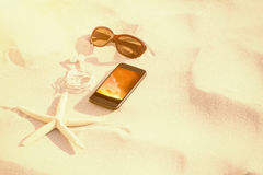 Composite image of starfish with sunglasses and mobile phone kept on sand Stock Image