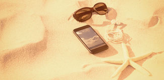 Composite image of starfish with sunglasses and mobile phone kept on sand Royalty Free Stock Image