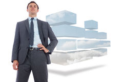 Composite image of stern businessman with hand on hip Stock Photos