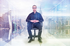 Composite image of stern businessman sitting on an office chair Stock Photo