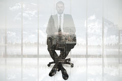 Composite image of stern businessman sitting on an office chair. Stern businessman sitting on an office chair  against new york Royalty Free Stock Photography