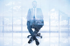 Composite image of stern businessman sitting on an office chair. Stern businessman sitting on an office chair  against new york Stock Photos