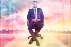 Composite image of stern businessman sitting on an office chair. Stern businessman sitting on an office chair  against server room with towers Royalty Free Stock Photos