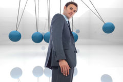 Composite image of stern businessman standing. Stern businessman standing against blue newtons cradle Royalty Free Stock Photo