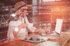 Composite image of stocks and shares. Stocks and shares against woman having coffee while using laptop in cafe royalty free stock image