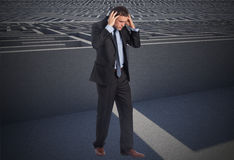 Composite image of stressed businessman with hands on head Royalty Free Stock Image